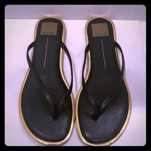 Black leather flip flops with gold detailing
